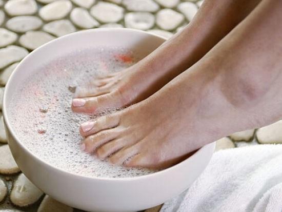 распаривает ноги в воде